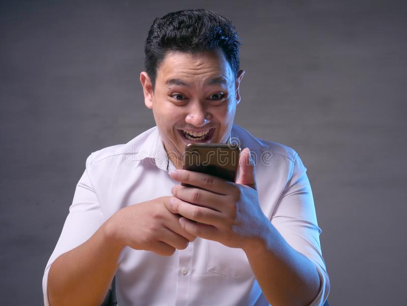 Young Man Texting Reading Chatting on His Phone, Smiling Happy stock images