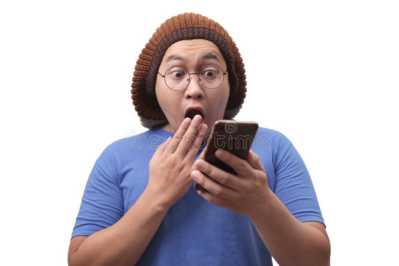 Young Man Texting Reading Chatting on His Phone Surprised Gesture. Attractive young Asian man reading texting chatting  on his phone, shocked surprised stock photos