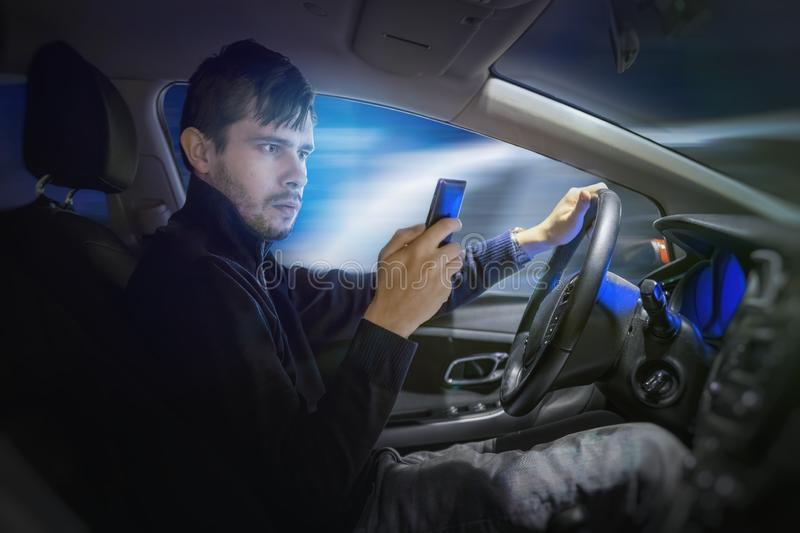 Young man is texting using smartphone and driving a car at night. stock images