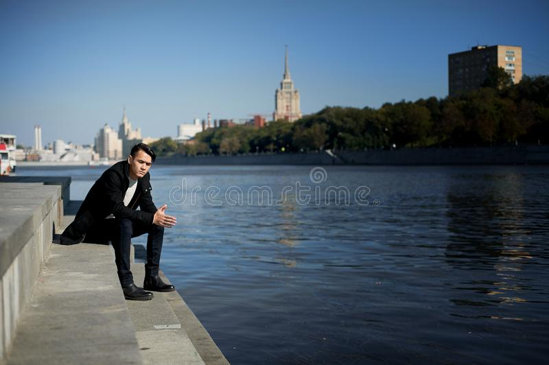 A young man, thin. With dark hair and brown eyes. Sitting on the steps near the water. Sad. People in the big city stock photo