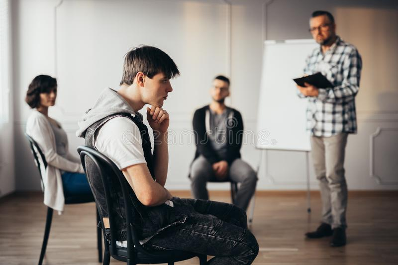 Young man thinking about an answear during group coaching session. Young men thinking about an answear during group session royalty free stock photo