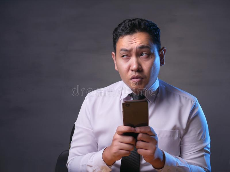 Young Man Thinking While Chatting on Smart Phone royalty free stock photos