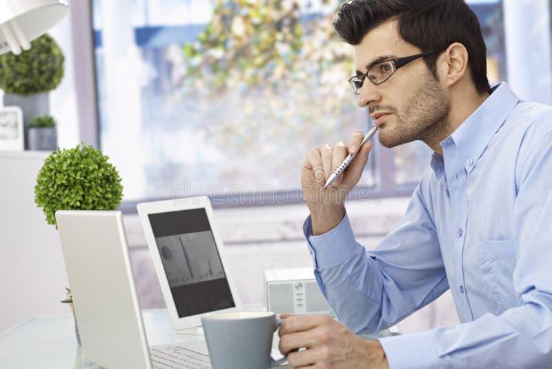 Young man thinking at desk stock photo