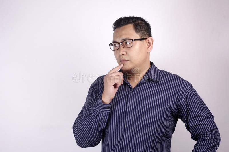 Young Man Thinking Expression, Looking to The Side. Young Asian man wearing blue shirt thinking gesture, looking to the side. Close up body portrait against stock photos