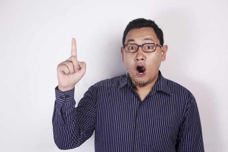 Young Man Thinking and Looking Up, Having Good Idea, with Mouth Open. Photo image of young Asian man looked happy thinking and looking up with mouth opened stock image