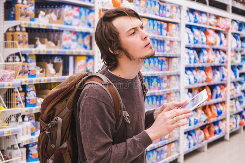 Young man is thinking about shopping with a tablet selects household chemicals in a supermarket stock images