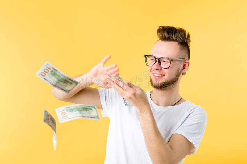 Young man throwing bills wealth money waste. Smiling young man bearded hipster holding dollar bills bunch throwing banknotes in air. Wealth luxury casino money royalty free stock images