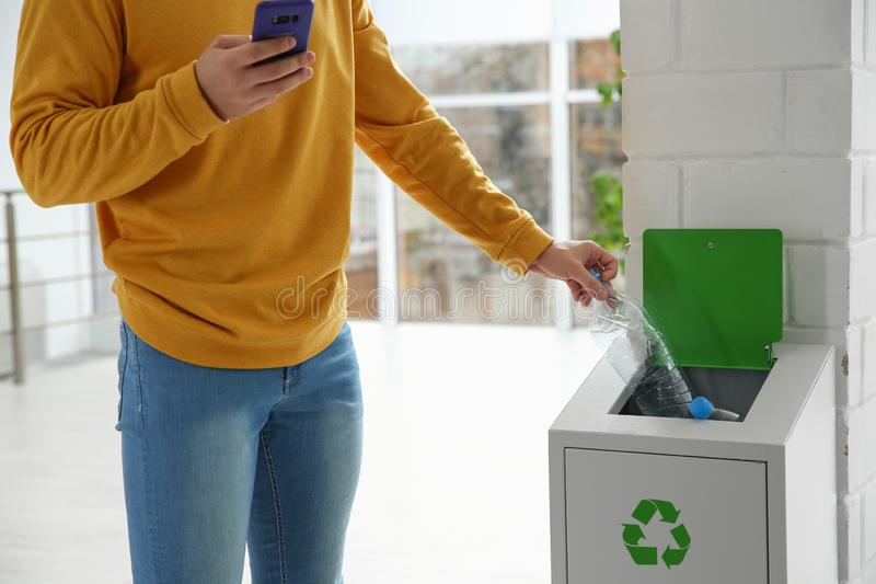 Young man throwing empty plastic bottle in metal bin indoors, closeup. Waste recycling stock photos