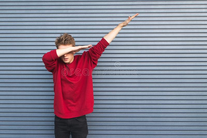 Man throws dab on the background of a gray wall. Young man throws dab on the background of a gray wall stock images