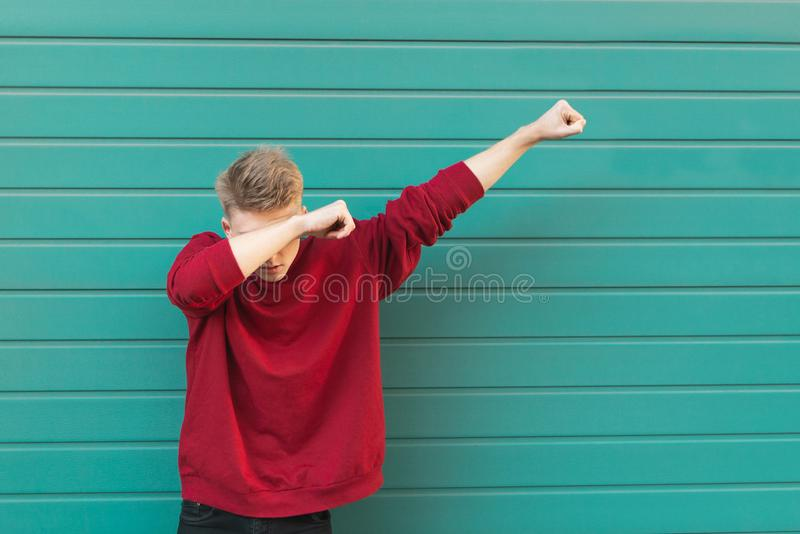 Man throws dab on the background of a turquoise wall. Young man throws dab on the background of a turquoise wall royalty free stock images