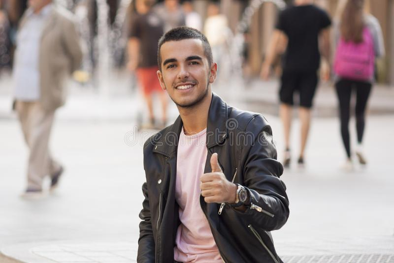 Young man thumbs up in the street and looking at camera royalty free stock images