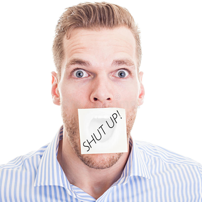 Young man told to shut up. Young man wearing blue and white striped shirt with post it note marked with text'shut up', white background royalty free stock image