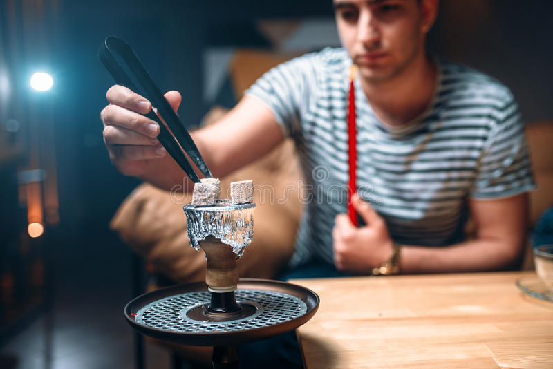 Young man with tongs kindle the coal at hookah bar stock images