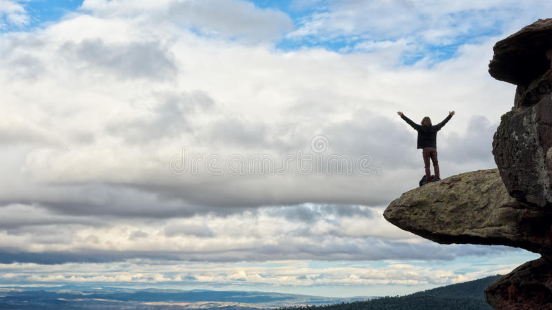 Young man on top of a cliff stock image
