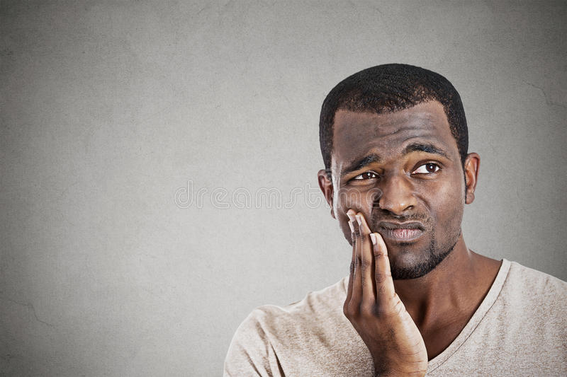 Young man touching face having really bad pain tooth ache. Closeup portrait handsome young man touching face having really bad pain tooth ache isolated gray wall royalty free stock image