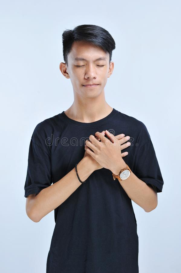 A young man is touching her heart for humanitarian solidarity with closed eyes and grateful gesture on face. Health concept. Over grey background royalty free stock images