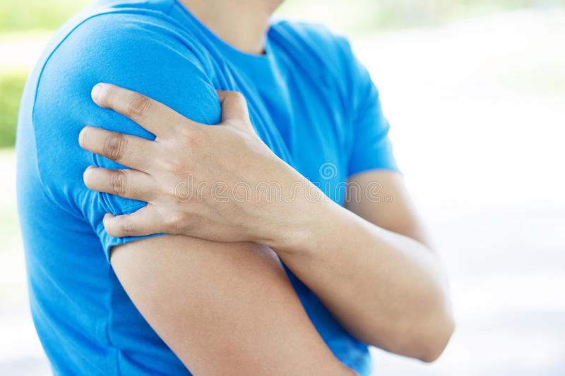 Young man touching painful twisted or broken shoulder. Athlete training accident. Sport Exercise is not warm, causing injury. and. Pain with arm bones. Health stock images