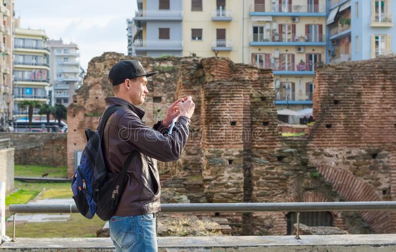 Young man, tourist, with backpack taking picture on a smartphone the Palace of Galerius stock photo