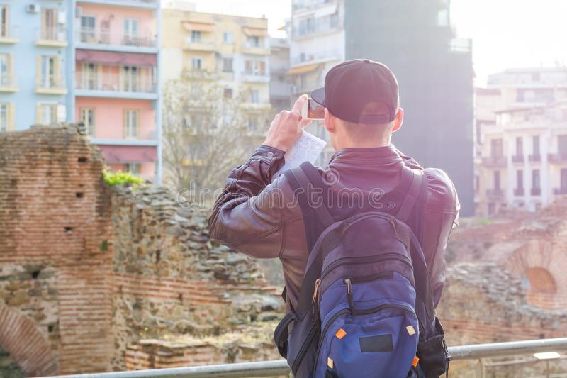 Young man, tourist, with backpack taking picture on a smartphone the Palace of Galerius at sunset stock images