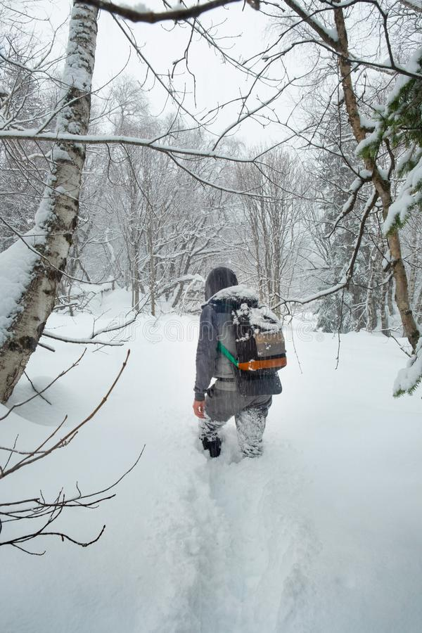 Young man tourist with a backpack walks through deep friable snow in the winter royalty free stock photography