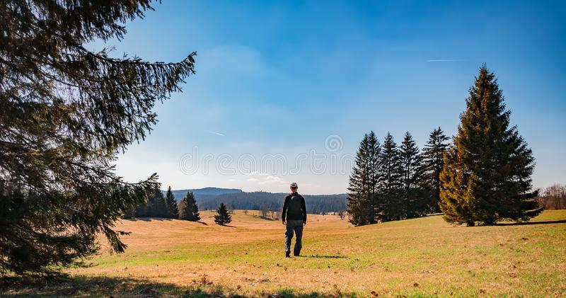 Young man tourist with backpack and white cap stand in czech landscape with trees and blue sky.  royalty free stock photo
