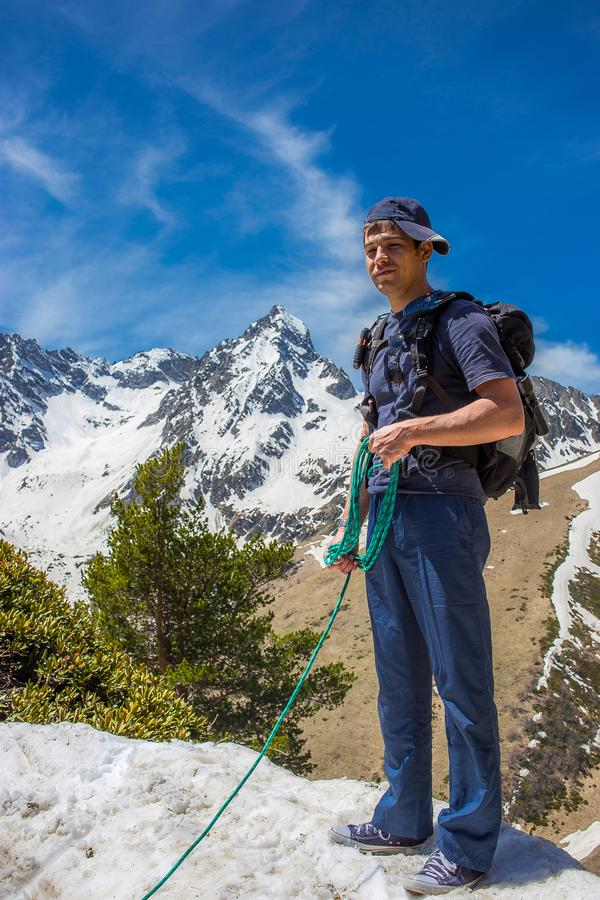 A young man tourist in blue clothes with a backpack is standing in the mountains next to the snow stock photo