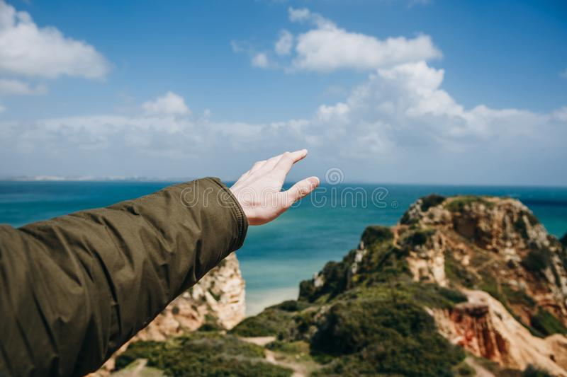 A young man tourist enjoys beautiful views of the Atlantic Ocean and the landscape. Young man tourist with a backpack enjoying beautiful views of the Atlantic royalty free stock photo