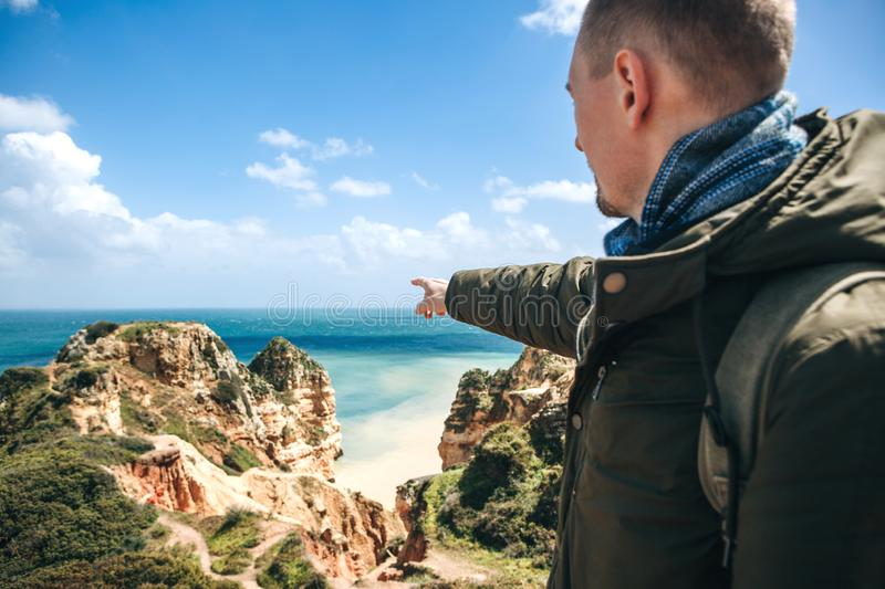 A young man tourist enjoys beautiful views of the Atlantic Ocean and the landscape. Young man tourist with a backpack enjoying beautiful views of the Atlantic stock photos