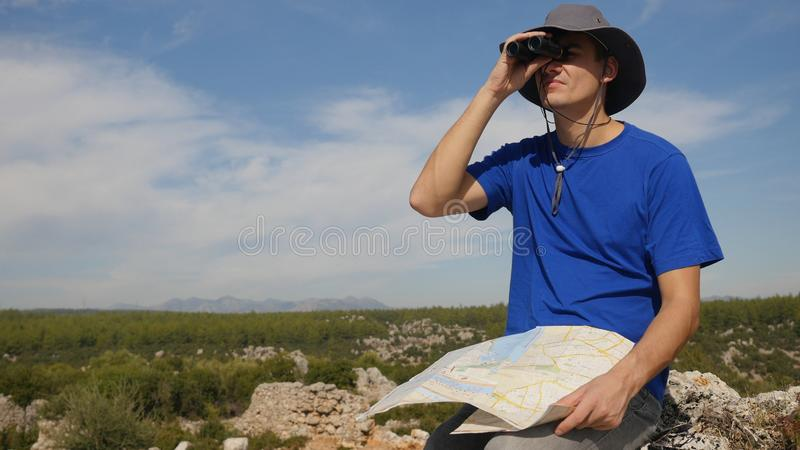 Young man traveler with map looking far away through binoculars. Young man tourist in panama hat with map looking far away through binoculars sitting on ancinet stock photography