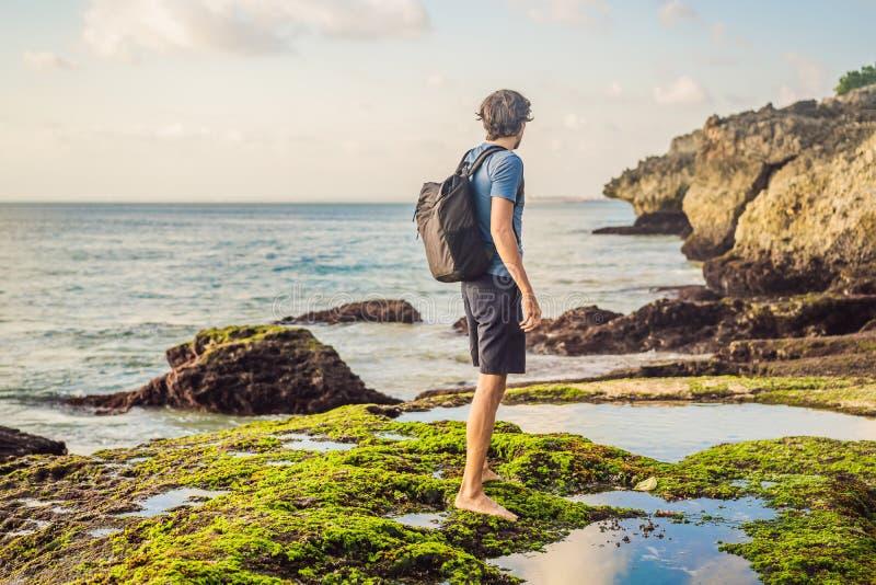 Young man tourist on Pantai Tegal Wangi Beach, Bali Island, Indonesia. Bali Travel Concept.  stock photo