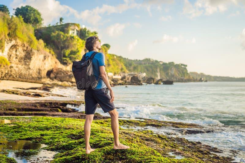 Young man tourist on Pantai Tegal Wangi Beach, Bali Island, Indonesia. Bali Travel Concept.  royalty free stock image