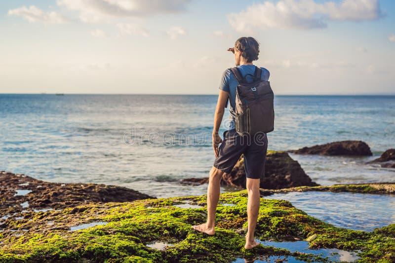 Young man tourist on Pantai Tegal Wangi Beach, Bali Island, Indonesia. Bali Travel Concept.  royalty free stock photo