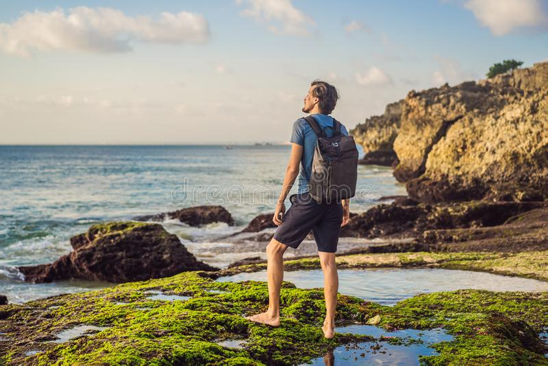 Young man tourist on Pantai Tegal Wangi Beach, Bali Island, Indonesia. Bali Travel Concept.  stock image