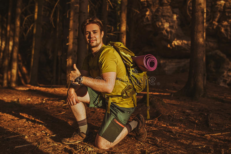 Young man tourist. Showing thumbs up hand sign in forest at red sunset light stock photo