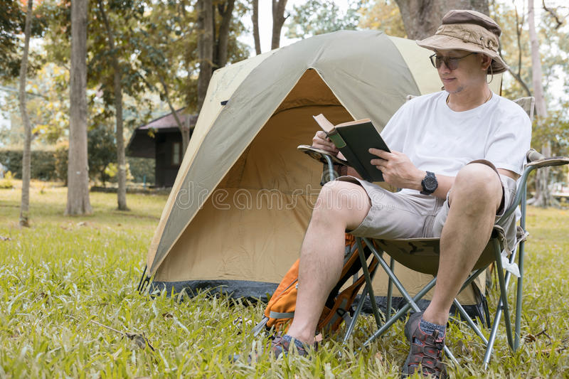 Young man tourist sitting on chair and reading book in front of royalty free stock photography
