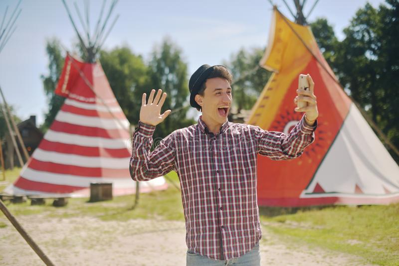 Young man tourist take photo selfie / video communication and smiling on the background teepee / tipi- native indian house. Man in stock photo