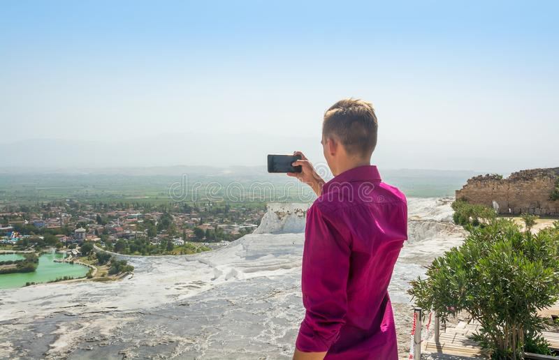 Young man, tourist, takes pictures with his mobile phone view Pa stock image