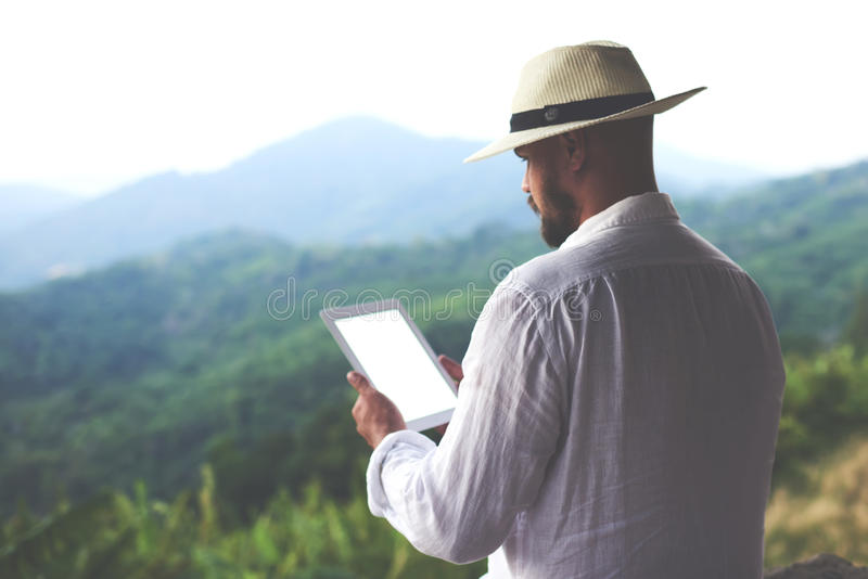 Young man tourist is using touch pad,while is standing against jungle view. Hipster guy is holding digital tablet with copy space on the screen for your royalty free stock image