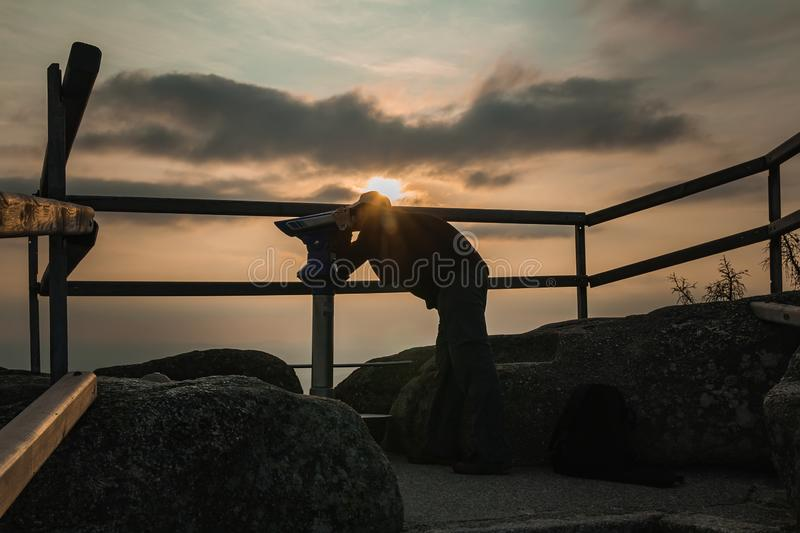 Young man tourist in white cap watching to telescope on lookout Tristolicnik at sunset, Sumava National Park and Bavarian Forest, royalty free stock photo