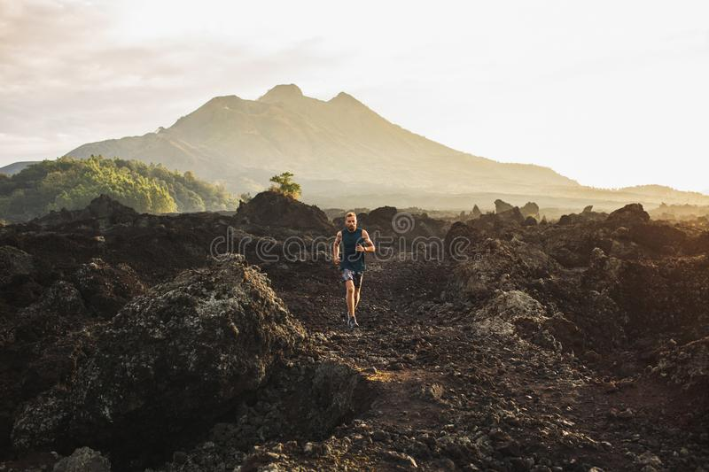 Young man trail running in mountains in morning. Young athlete man trail running in mountains in the morning. Amazing volcanic landscape of Bali mount Batur on royalty free stock image
