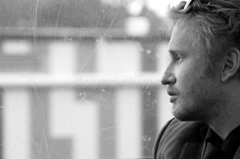Young man on train trip looking out window daydreaming royalty free stock photography