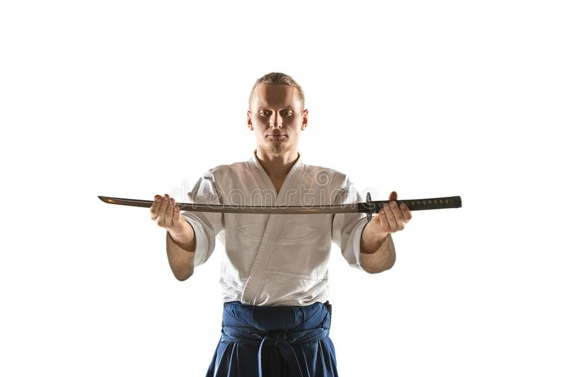 The young man are training Aikido at studio. The young man are training in Aikido at studio with saber.Aikido master practices defense posture. Healthy lifestyle stock photos