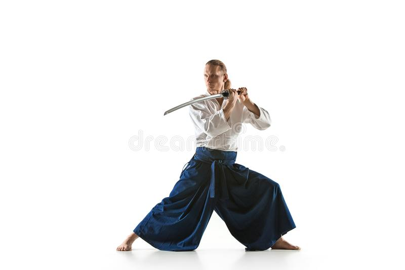 The young man are training Aikido at studio. The young man are training in Aikido at studio with saber.Aikido master practices defense posture. Healthy lifestyle stock photography