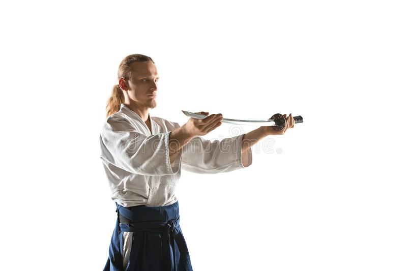 The young man are training Aikido at studio. The young man are training in Aikido at studio with saber.Aikido master practices defense posture. Healthy lifestyle stock image