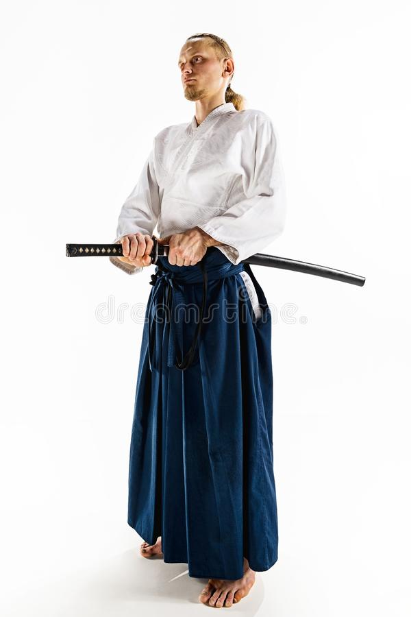 The young man are training Aikido at studio. The young man are training in Aikido at studio with saber.Aikido master practices defense posture. Healthy lifestyle royalty free stock image