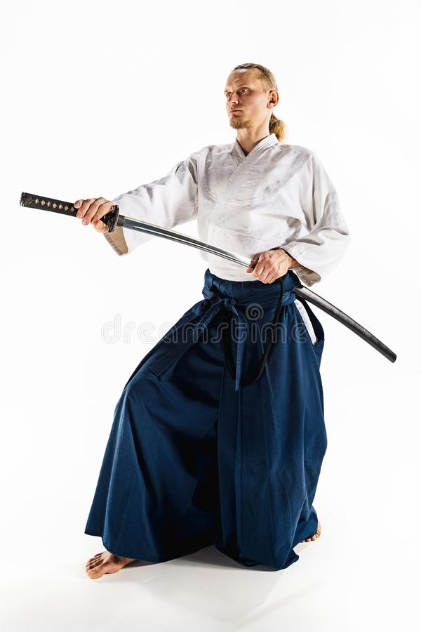 The young man are training Aikido at studio. The young man are training in Aikido at studio with saber.Aikido master practices defense posture. Healthy lifestyle stock photo