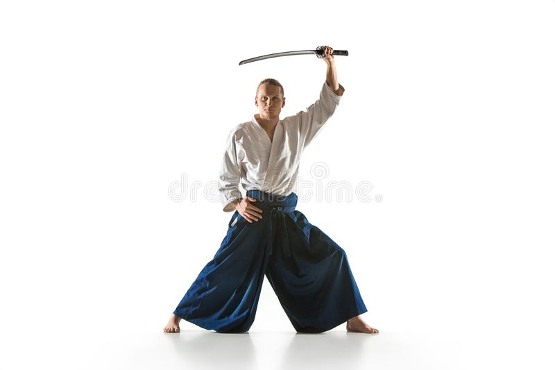 The young man are training Aikido at studio. The young man are training in Aikido at studio with saber.Aikido master practices defense posture. Healthy lifestyle royalty free stock photos