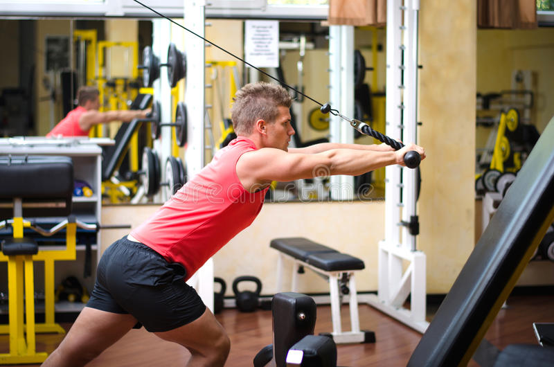 Young man training on gym equipment royalty free stock images
