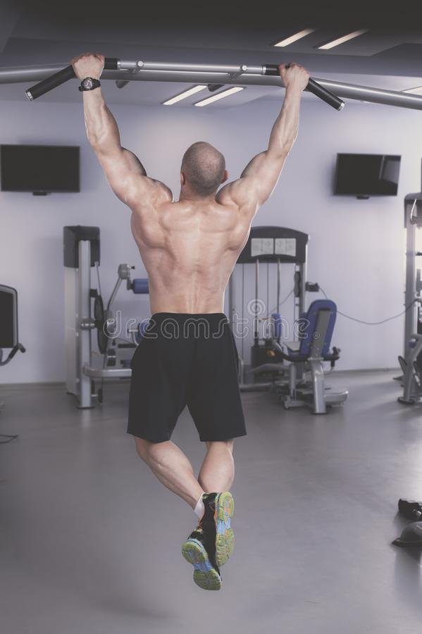 Young man training at gym with exercises . Young man stock photography