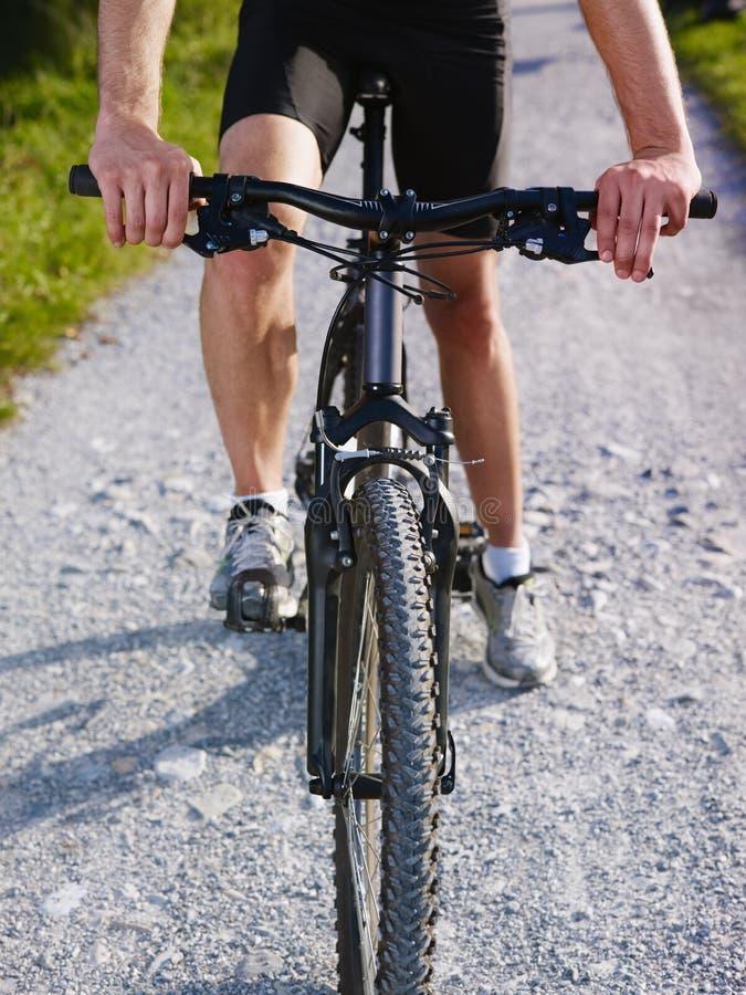Young man training on mountain bike stock photography